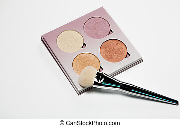 Set of highlighters with makeup brush over a white background