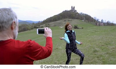 Active senior runners in nature taking photo with smart...