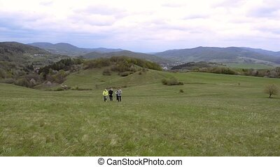 Group of seniors running outside up the green hills. - Group...