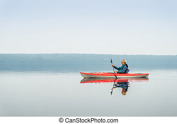 Woman happy to paddle from red kayak on calm lake