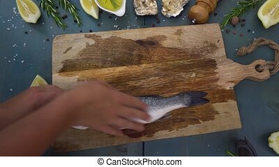 Taking and showing raw fish - Someones hands placing and...