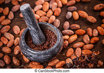 Cocoa beans being ground in mortar and pestle