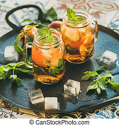 Summer refreshing cold peach ice tea with mint, square crop...