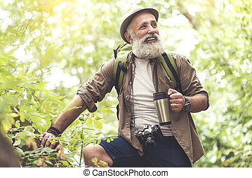 Cheerful senior male traveler drinking beverage after hiking...