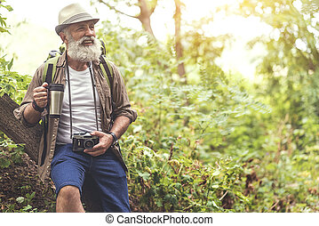 Happy old man resting after walking in woodland - Portrait...