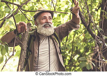 Joyful old male hiker making his way through branches in...