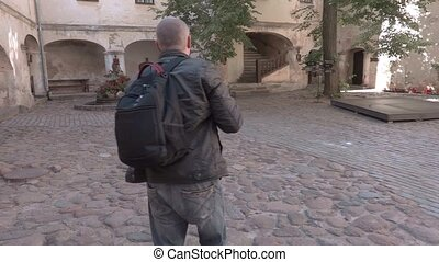 Tourist using tablet in the castle yard