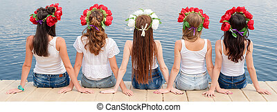 Back view of five young ladies, wearing flower wreaths,...