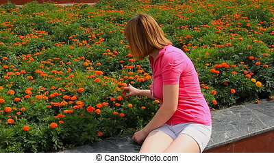 Young girl looking at marigold flowers