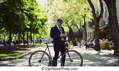 Mature businessman with smartphone and bicycle in the city....