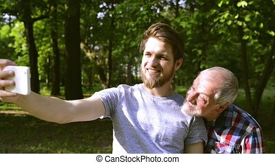 Hipster son and his senior father in park taking selfie. -...