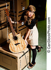 beautiful young woman with a classical guitar in a warehouse...