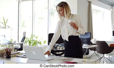 Businesswoman with coffee in her office working on laptop. -...