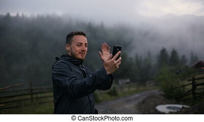 A young man in the evening in the mountains communicates on...