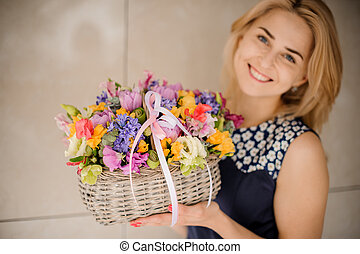 Pretty blonde girl with basket of different flowers