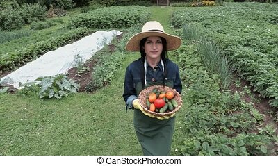 Female gardener with basket of tomatoes and cucumbers