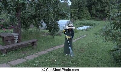 Female gardener using rake in the garden