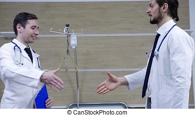 Slow motion of doctors shaking hands in the hospital room....