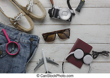 Top view of accessories to travel with fashion women clothing concept background.Several essential items for girl or teenage and adult.Mix of variety object on modern rustic white wooden office desk.