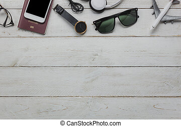 Top view of accessories essential to travel and technology background concept. Several of items for teenage or adult for traveler. Mix variety the objects on modern rustic white wooden office desk.