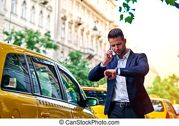 Young businessman talking on a phone and waiting for his...