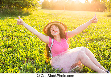 Beautiful young laughing naughty woman sitting on the grass...
