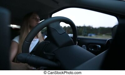 Confident woman driving car in city street - Young beautiful...
