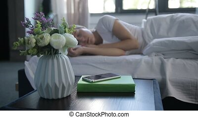 Sleepy woman turning off mobile alarm clock - Beautiful calm...