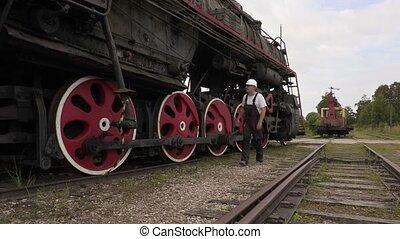 Railway employee walking near locomotive on rails