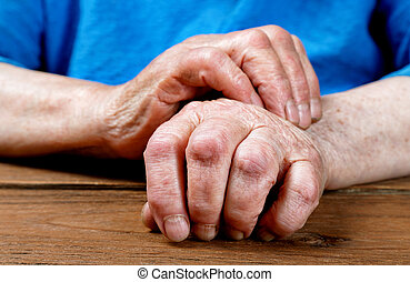 Hands of an old woman close-up on a table
