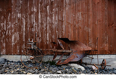 an old and rusty horse plow in front of a weathered wooden barn wall