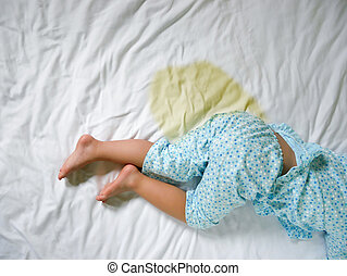 Bedwetting: Child pee on a mattress,Little girl feet and pee...