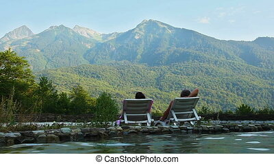 ?ouple relaxes lying by the lake in the background of the mountains.