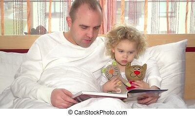 Playful dad reading book and playing with his young daughter girl