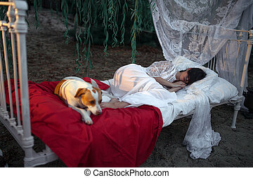 Young woman with dog lies on bed with bedding and baldachin...