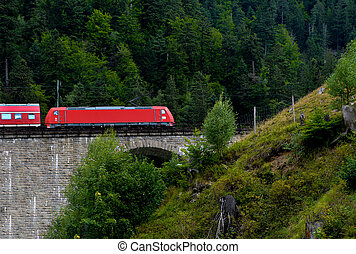 red train on stone trestle in Germany - bold red train on...