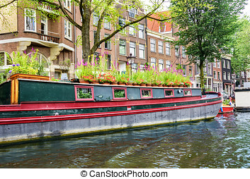 Houseboat in Amsterdam - Large houseboat anchored on a canal...