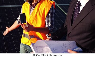 View of an engineer showing photovoltaic detail to client at...