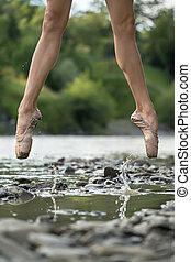 Ballerina jumping in river
