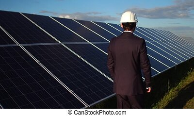 Businessman choosing alternative energy, walking at solar...
