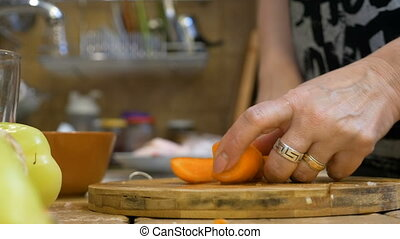 Adult woman wife in kitchen cutting fresh carrot preparing a...
