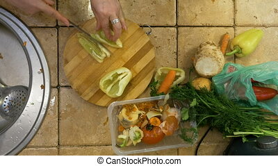 Top view of caring adult housewife cutting vegetables in...