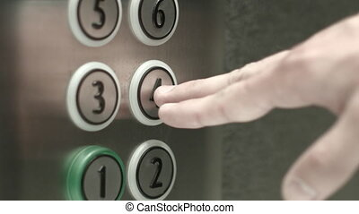 Man presses a button the fourth floor in an elevator - Man...