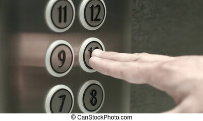 Man presses a button the tenth floor in an elevator - Man...
