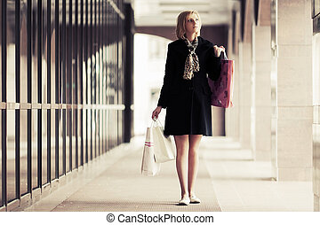 Happy young fashion woman with shopping bags in the mall