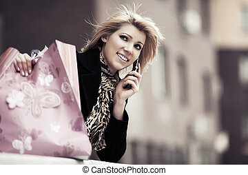 Fashion woman with shopping bags calling on mobile phone