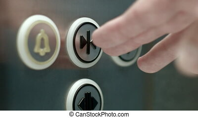 Man pushes a button opening elevator doors. Close up - A man...