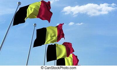 Row of waving flags of Belgium agaist blue sky, seamless loop