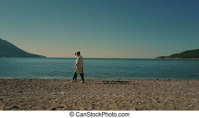 Couple Relaxed boyfriend taking girlfriend on hands twisting on seashore walking on sea shore holding hands looking into distance.