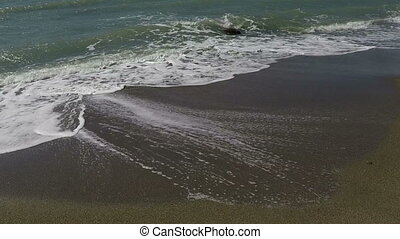 Waves On The Sand - Sea waves on golden sand at the shore,...